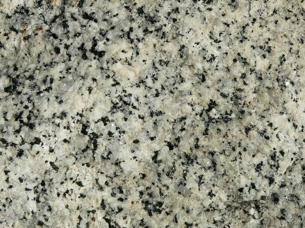 A closeup view of granite, a rock.  It is composite of small grains of the minerals quartz (white) and feldspar (black).  These mineral grains would also be considered crystals.  This would granite would also be considered a stone, particularly when it was going to be carved or used as a building material.