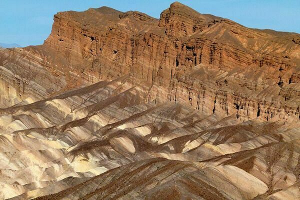This is a sedimentary rock formation that's part of Zabriskie Point, located within Death Valley, California. It's composed of sediments from Furnace Creek Lake which dried up roughly 5 million years ago. Millions of years of erosion have left the sediment layers exposed.